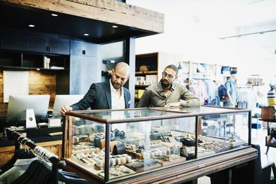 Customer looking at mens accessories with shop owner in mens boutique