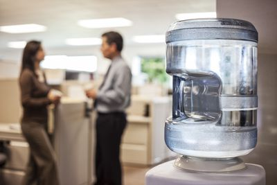 Water cooler in an office with employees talking in the background