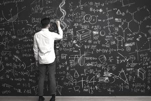 Man writing a long mathematical equation on a chalkboard