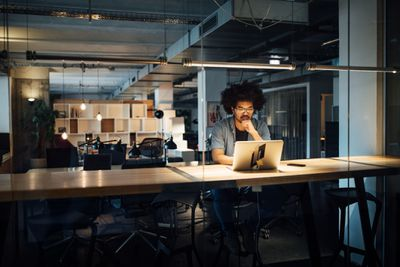 man working in a dark office by himself on a laptop with a lamp on