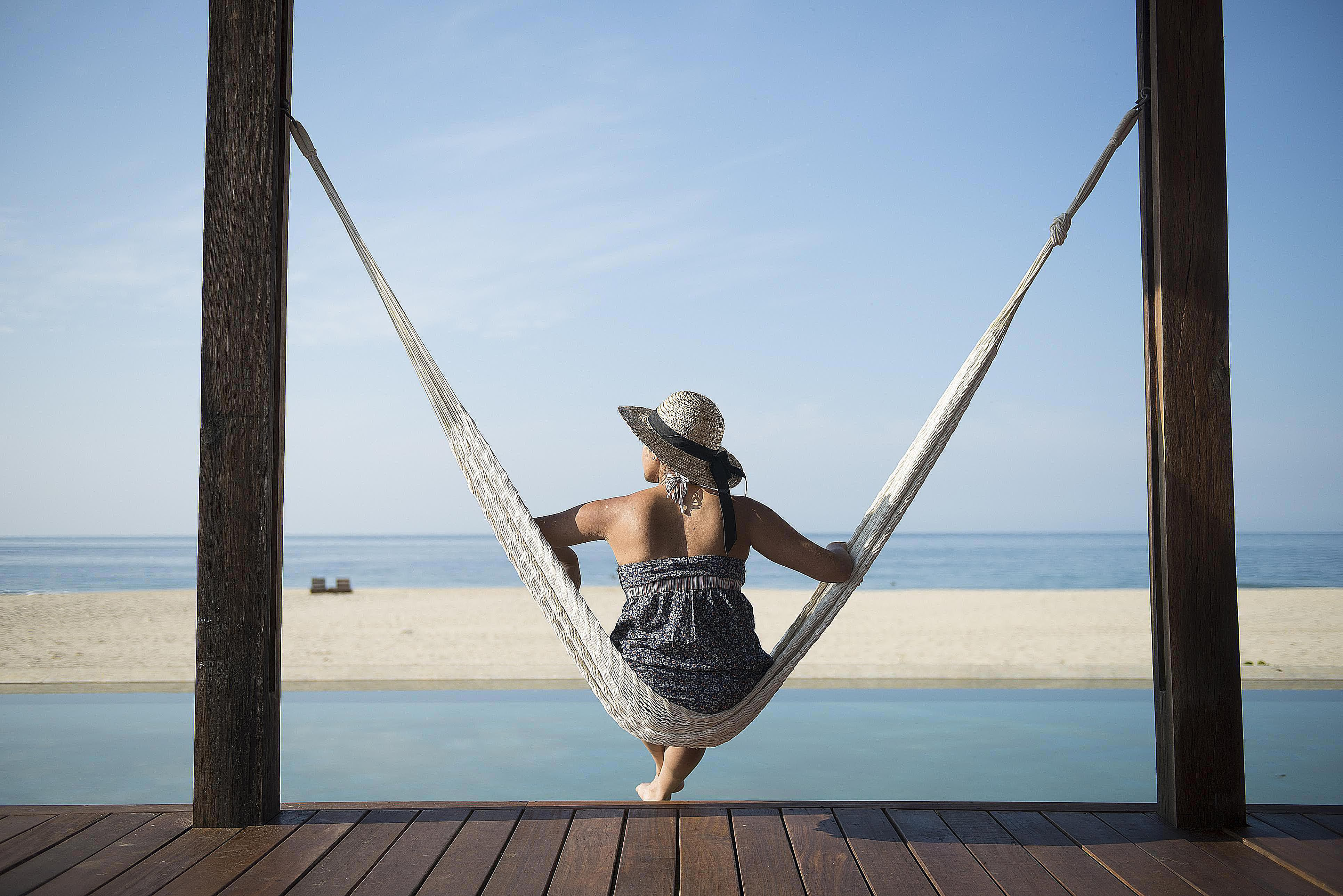 Woman sitting in hammock looking out at sunny beach