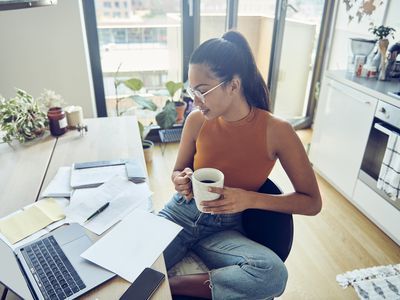 Close up of beautiful woman at her home, holds coffee cup and finishing paperwork