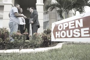 Couple shaking hands with real estate agent outside an open house