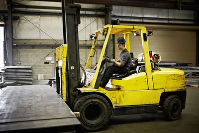Man driving a yellow forklift with steel sheets