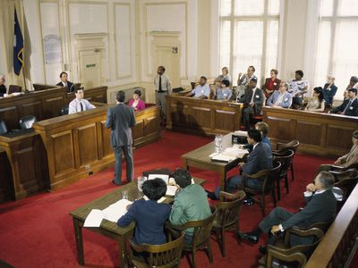 Courtroom scene with witness testifying, jury, and spectators