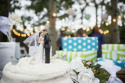 Bride and groom cake topper on cake.