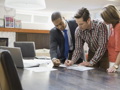 The incorporator of a business signing documents in a modern office with two people witnessing their signature.