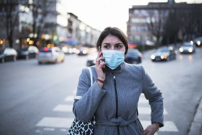 Woman wearing mask and talking on a cell phone