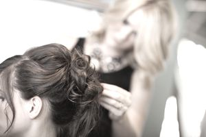 a close up of a hairdresser working on a client's hair
