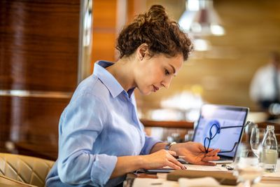 Female small business owner making a financial report of her company from a pie chart on his laptop while sitting in an exclusive restaurant