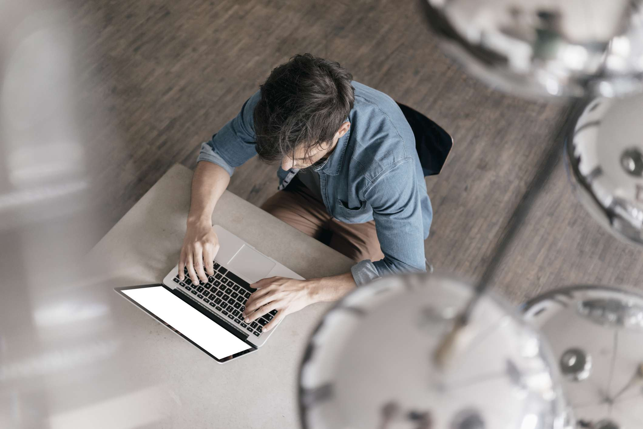 Young man working on laptop, top view