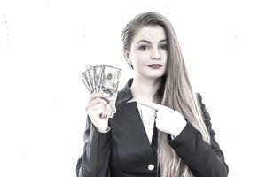 Woman holding up a lot of cash representing a referral fee.