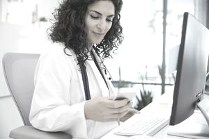 Female doctor sitting at desk using smart phone