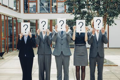 Business people holding question marks in front of their faces representing the question of whether they are classified as employees or independent contractors.