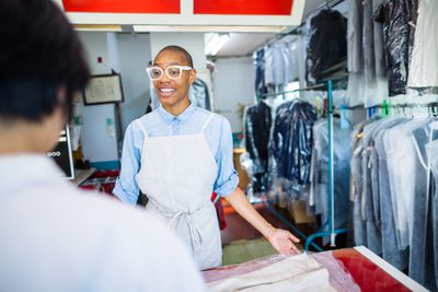 A young woman is working at a dry cleaning shop and talking to a customer.