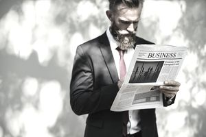 A businessman reading the business section of a newspaper