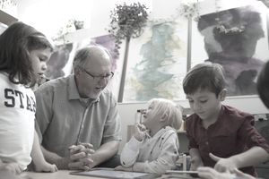 Elderly volunteer helping children with art project.
