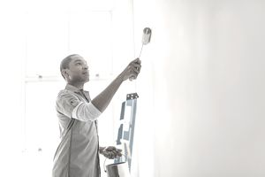 A man applying a coat of paint to a wall