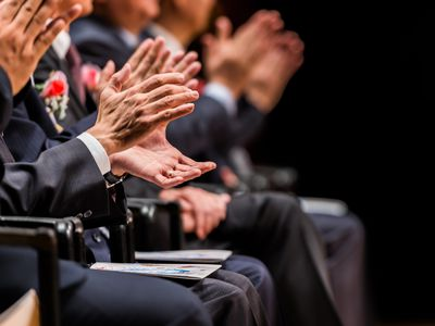 Businessmen clapping during the annual meeting of a corporation.