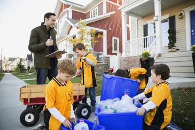 Man with kids in sports uniforms filling recycling tubs