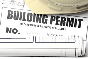 Building permit with hardhat and blueprints