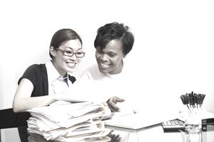 2 women going over accounting paperwork.