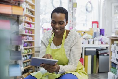 Female small business owner taking inventory with digital tablet