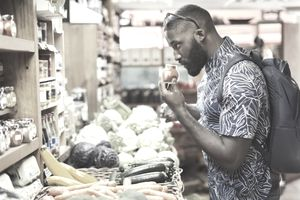 Man shopping, smelling spices in grocery store
