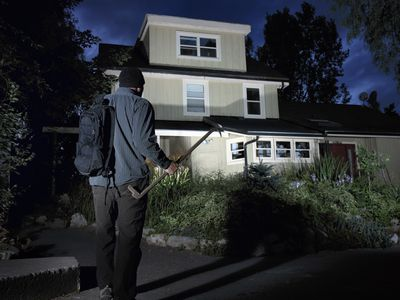 Burglar approaching a home at night holding a large crowbar