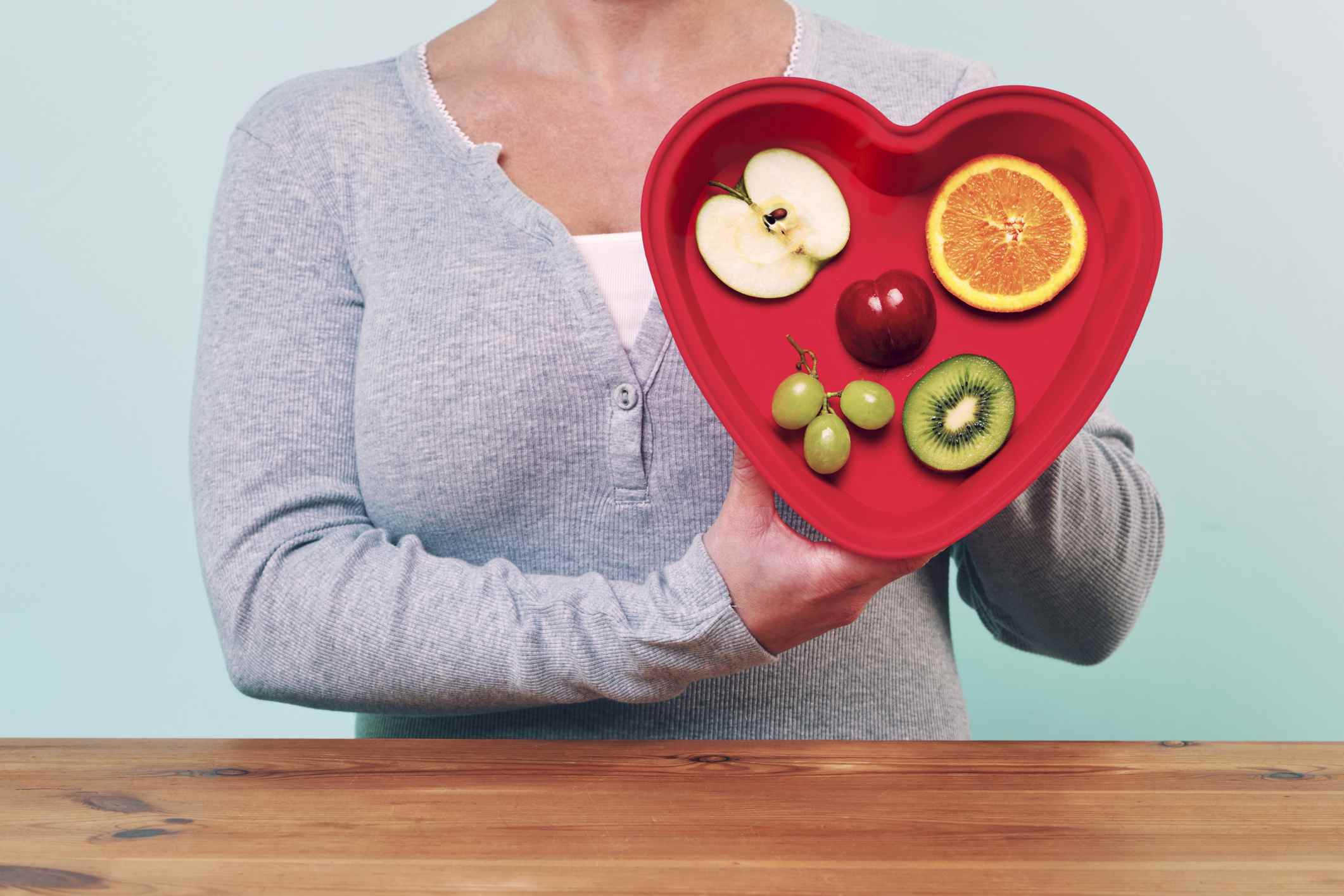 woman holding a red heart-shaped dish with different fruits on it