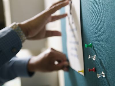 Pushpins in a bulletin board with hands pinning up a piece of paper