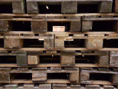 Wooden pallets stacked on top of one another waiting for use.