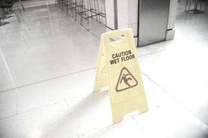 A yellow sign reading wet floor on the floor of a restaurant, such warnings can limit liability.