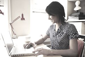 Young woman using laptop in creative office space