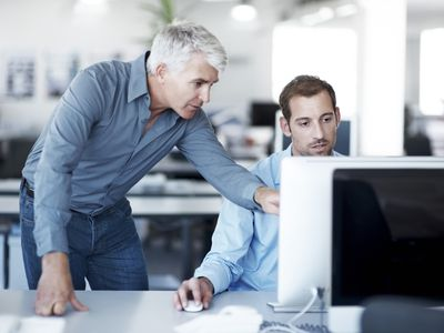 A Quickbooks consultant standing over a business owner pointing out Quickbook tips at a computer