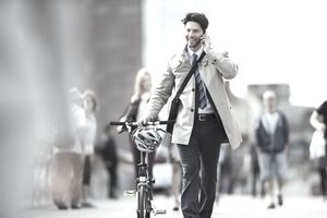 Businessman talking on cell phone pushing bicycle in city