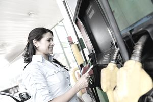 Woman pays at gas station pump using debit or credit card