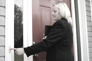 A saleswoman rings a doorbell.