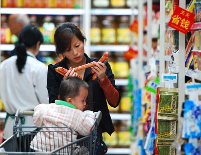 Woman with a shopping cart in a Chinese retail store.