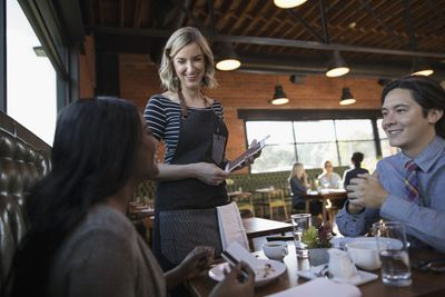 Couple Dining Paying Server With Digital Tablet Credit Card Swiper At Restaurant Table