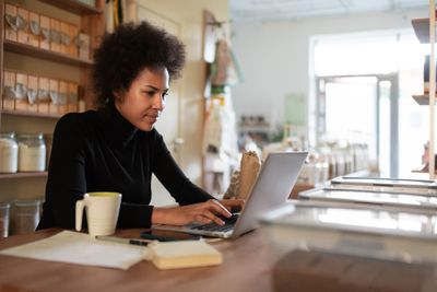 business owner in black turtleneck sitting in office looking at computer