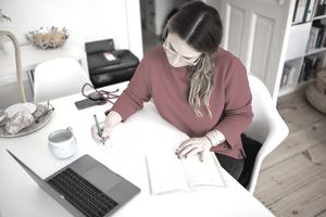 person in red sweater writing notes from a book at a desk