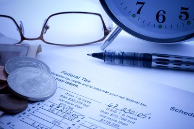A closeup of eyeglasses, a pen, some change and a clock sitting atop a federal tax return