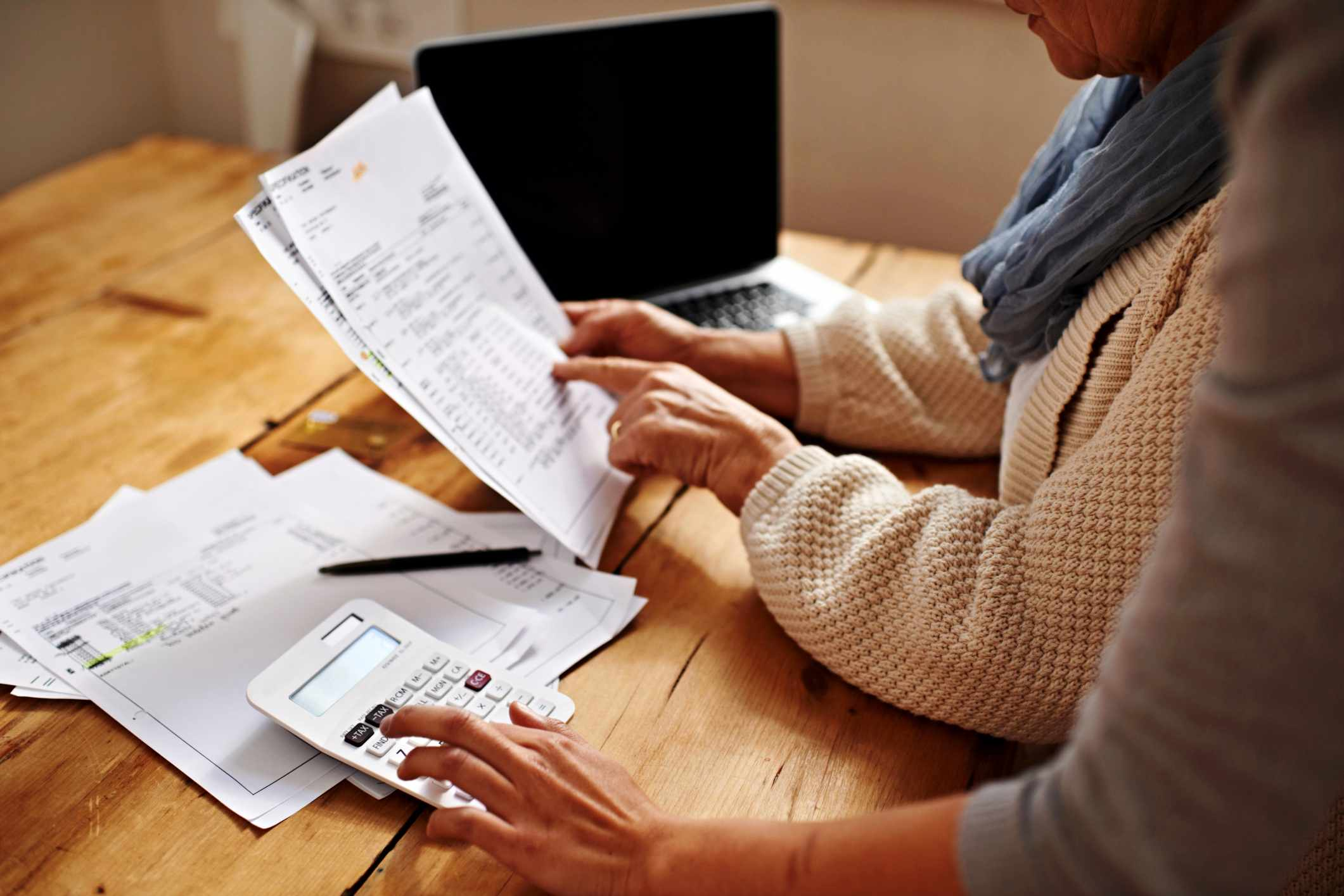 Two women entering income tax receipts on laptop