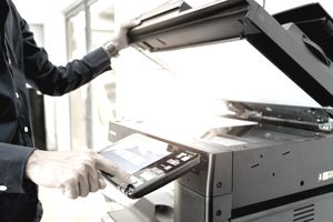 Businessman using an office copier to make duplicates of an advertisement for mailing to clients.