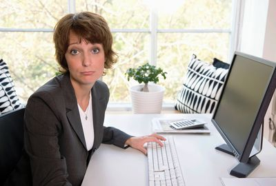 Middle aged woman at desk with computer.
