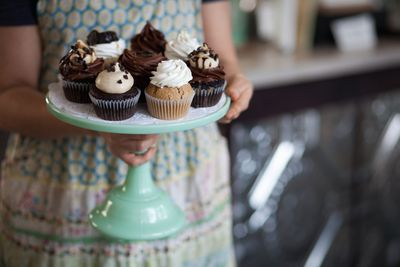 a woman holding a tray of cupcakes
