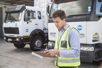 Department of Transportation worker holding clipboard conducting inspections on commercial vehicles