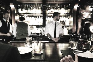 Bartenders working behind a busy bar.