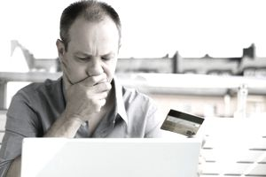Man thinking while holding credit card before laptop